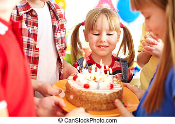 Birthday tradition - Cute girl looking at birthday cake with...