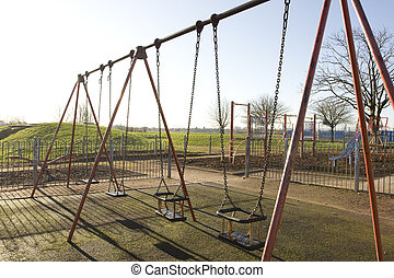 swings in a children\\\'s playground on a winters day
