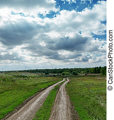 dirty road to horizon under dramatic sky