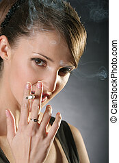 Smoking woman - Beautiful young woman smoking over dark soft...