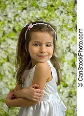Portrait of pretty 5-year-old girl on a background of green