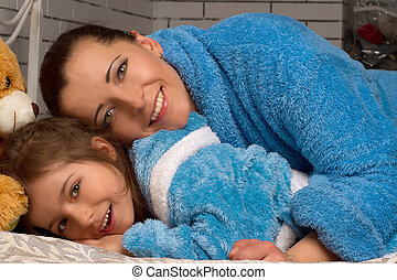 Mom and daughter in the same blue terry robe