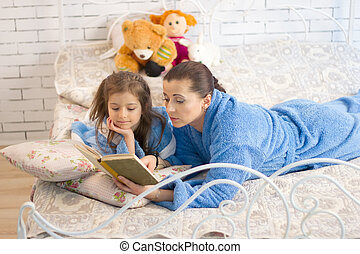 Mom and daughter reading a book - Mom and daughter in the...
