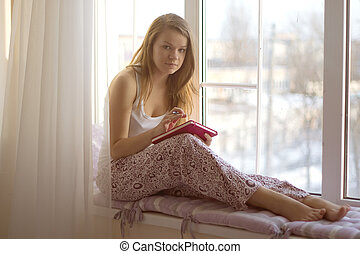 Young girl on a window sill in his pajamas writing in a...
