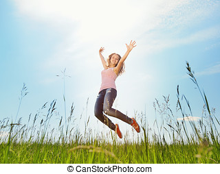 Spring Girl - The girl jumps on a green grass