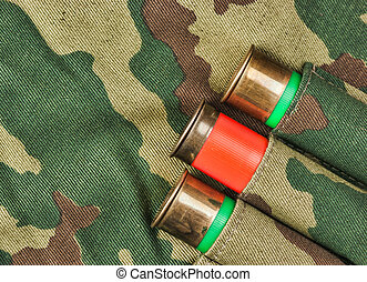 Old hunting cartridges and bandoleer on camouflage...