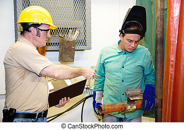 Supervisor on Factory Floor - Supervisor evaluating a metal...