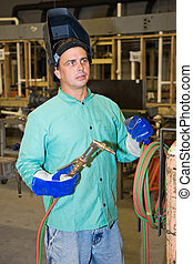 Welder on Factory Floor - Welder on factory floor of a metal...