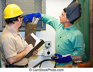 Welder with Supervisor - Welder in metal shop working while...
