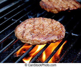 Burgers Sizzling On The Grill - Burgers cooking over flames...