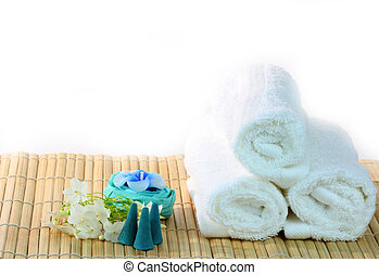 Spa with candles and towel on bamboo mat