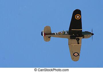 Spitfire flying high in blue sky