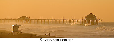 Two Surfers walk along the Beach in Huntington Beach at...