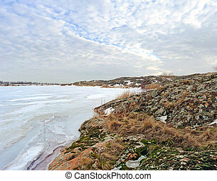 Winter, the frozen lake, a rocky shore