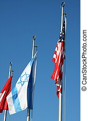 Israeli flag and American flag waving in the blue sky
