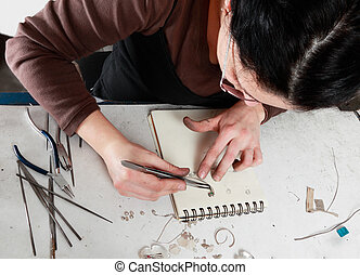 Female Jeweler Working - Bird eye view of a female jeweler...