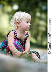 little girl sitting on the ground