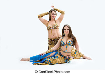 Two beautiful belly dancers dressed in gold and blue,...