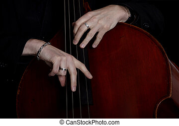 Contra bass player in front of black background - Contrabass...