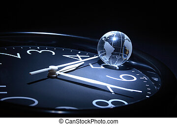Globe on clock - Litte glassy globe on dark background with...