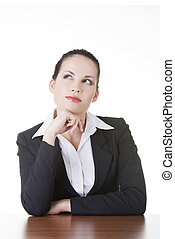 Pretty business woman in sitting at the desk and thinking,...