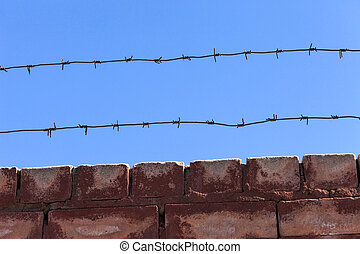 Barbed wire fence against blue sky