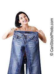 Young happy fit woman with big pants , isolated on white