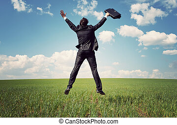businessman in suit jumping in field and holding the bag