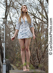 Leggy blond woman - Barefooted leggy blond woman posing like...