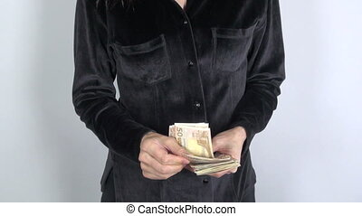 black shirt woman with big pile of - woman hand counting 50...