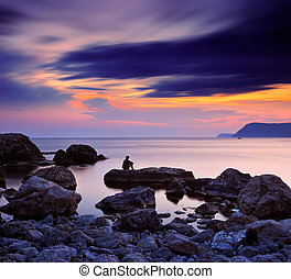 A man sitting on a rock by the sea