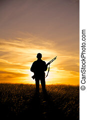 Woman Rifle Hunter at Sunset