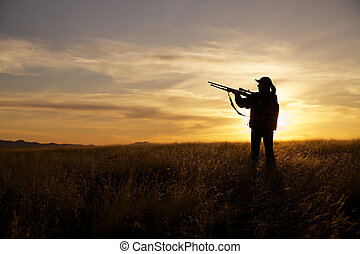 Ready to Shoot at Sunset - a woman hunter readies her rifle...