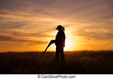 Woman with Shotgun in Sunset - a female bird hunter with...