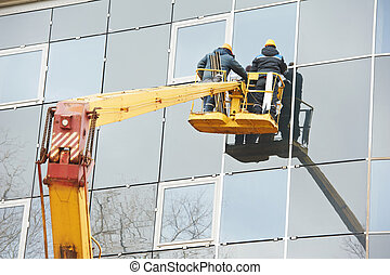 workers installing glass window on building - Tho builders...