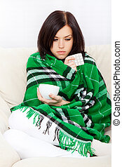 young woman - Ill woman covered with blanket holding cup of...