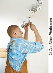 Electrician at wiring work - electrician working with cable...