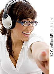 front view of smiling businesswoman pointing with headphones...