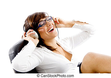 side view of smiling woman listening to music with white...