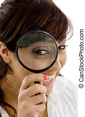 smiling female holding magnifier close to eye