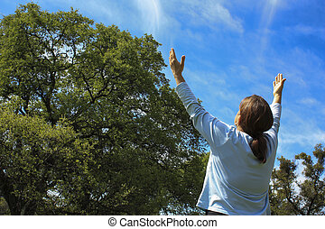 Woman Praising God with Oak Trees in the Background and blue...
