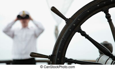 Sailor looking through binoculars - old wooden ship wheel in...