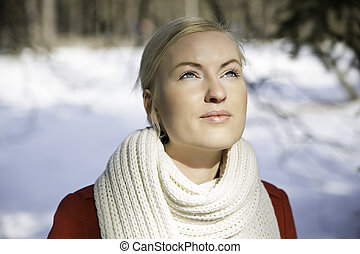 Zoomed woman warming face under sunlight at winter