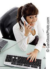 high angle view of smiling female executive interacting on phone  in an office