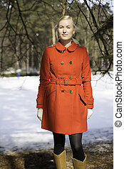 Young woman in red coat under spruce tops