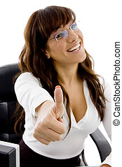 front view of smiling female executive with thumbs up