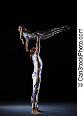 Circus artists perform different tricks Man holding woman