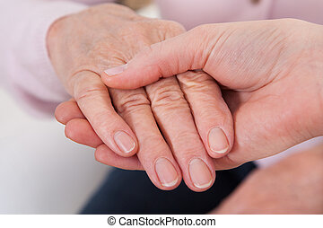 Young Woman Holding Senior Woman's Hand