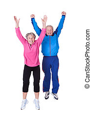 Portrait Of Senior Couple Jumping In Joy Over White...