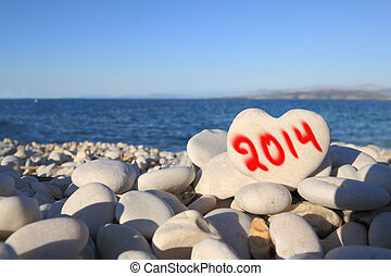 2014 new year written on heart shaped stone on the beach...